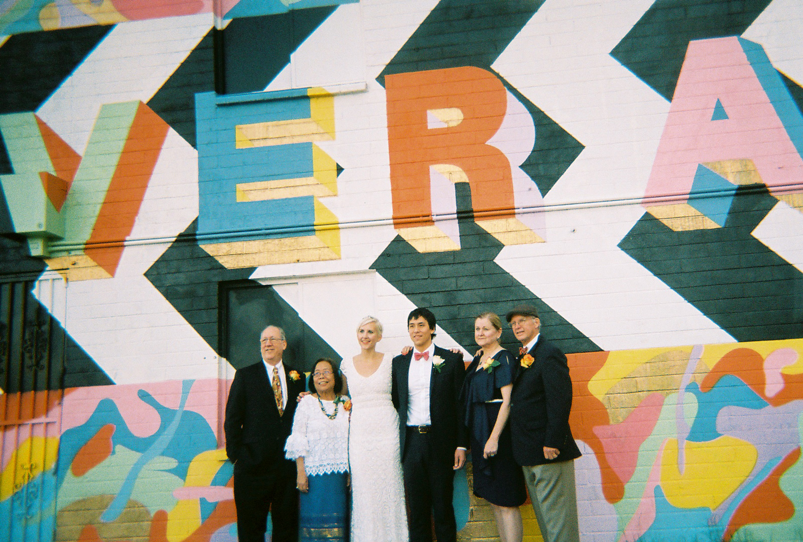 Bride & groom with parents in front of Ever After mural in downtown Las Vegas